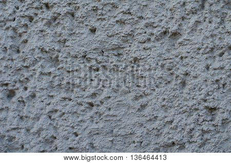 Background of a gray stucco coated and painted exterior rough cast of cement and concrete wall texture decorative coating