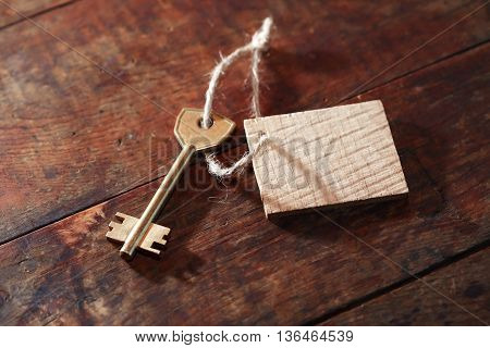 Key attached to blank tag with rope on wooden background