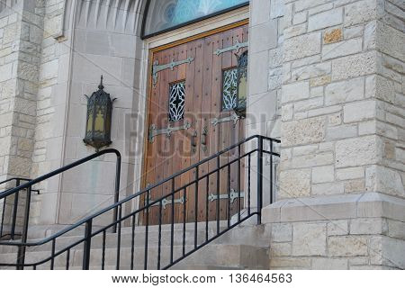 Steps leading to a wooden door of an old stone church in Michigan's Upper Peninsula.