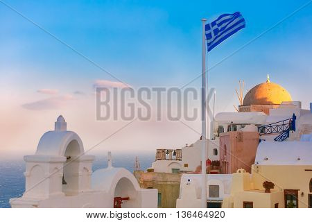 Picturesque view of white houses, church and Greek flag in the morning, Oia or Ia, island Santorini, Greece