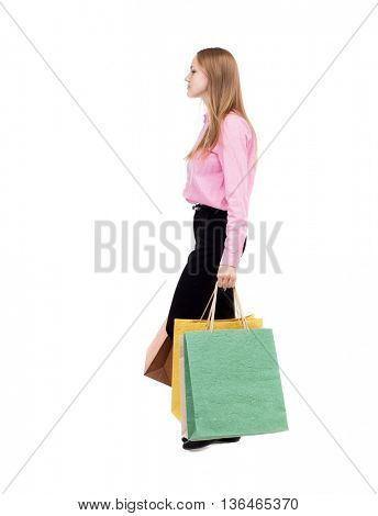 back view of going  woman  with shopping bags . beautiful girl in motion.  backside view of person.  Rear view people collection.  The girl in the pink shirt is bent under the weight of the bags.