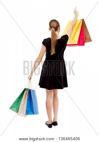 back view of woman  with shopping bags pointing . beautiful blonde girl in dress in motion.  backside view of person.  The blonde in a black short dress lifted in hand bags and showing thumb.
