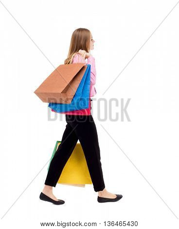 back view of going  woman  with shopping bags . beautiful girl in motion.  backside view of person.   throwing them on the shoulder.
