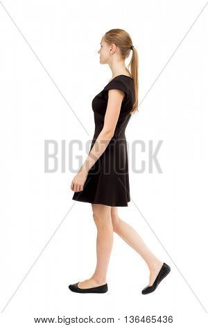 back view of walking  woman in dress. beautiful blonde girl in motion. backside view of person. Rear view people collection. Isolated over white background. blonde in a black short dress goes to right