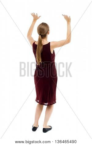 back view of woman  protects hands from what is falling from above. woMan holding heavy load Rear view people collection. backside view person. Blonde girl in burgundy dress holding something over him