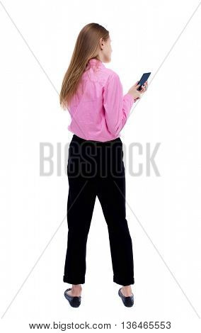 back view of standing young beautiful  woman  and using a mobile phone. girl  watching. Rear view people collection.    Isolated over white background. Turning left woman typing on the smartphone.