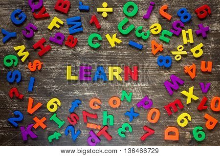 Learn written by plastic colorful letters on a wooden background