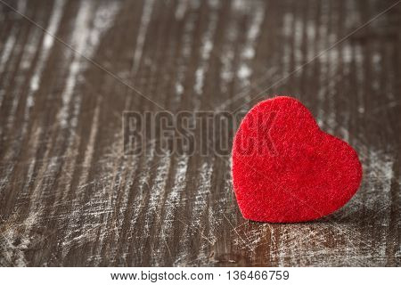 Old scratched wooden background with a small red heart