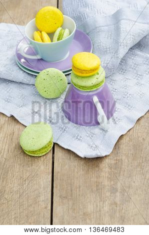 Rustic set of porcelain tea cups and homemade sweet macaroons on wooden background