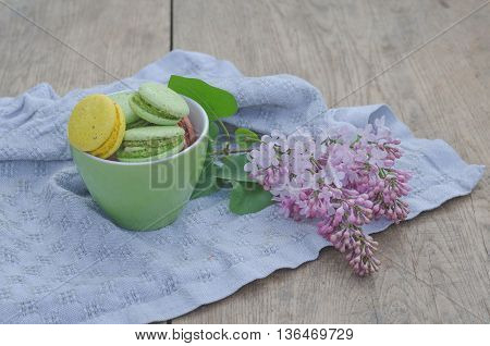 Sweet macaroons in porcelain teacups on a white crocheted napkin and lilac flowers