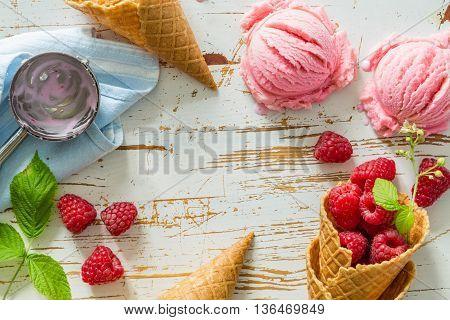 Raspberry ice cream on white wood background, top view