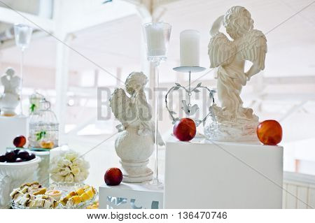 Decorated Figurines Of Angels And Candles On Wedding Reception