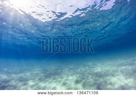Underwater shot of an infinite sandy sea bottom with clear blue water and waves on its surface