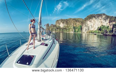 Young woman standing on the bow of yacht and looking to the rocky island