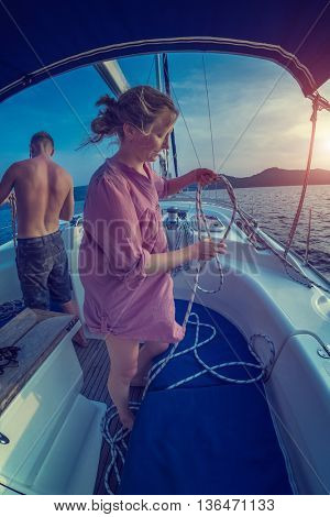 Young lady and man working with ropes on the sailing boat