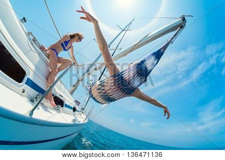 Two lady relaxing on the sail boat while sailing in the open sea. One of them laying in the hammock