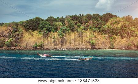 Aerial view of clear sea with traditional longtail thai boats and the island on the background