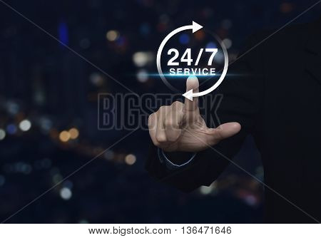 Businessman pressing button 24 hours service icon over blur light city tower background Full time service concept