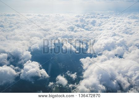 Sun, clouds and sky as seen through window of an aircraft