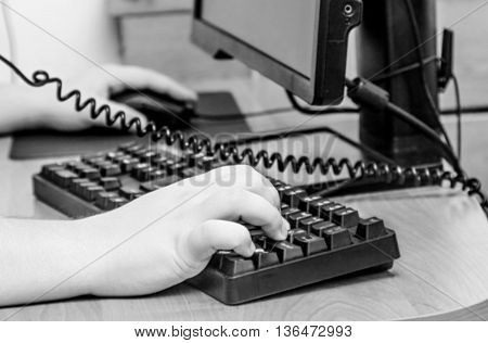 Hands on computer keyboard on wooden table in black and white colours
