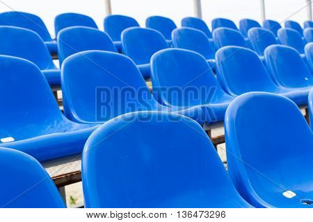 Empty plastic blue chairs at stadium in a row. Closeup.