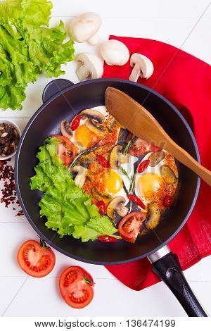 Fried eggs in pan with salad tomato pepper and spice on wooden background