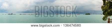 Panoramic view of the Singapore Strait from Sentosa Island. Ships, industrial landscape and stormy weather.