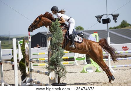 Turda, Cluj, Romania - June 19, 2016: An unidentified competitor jumps with her horse at the Salina Equines Horse Trophy , June 19, 2016 in Turda, Romania