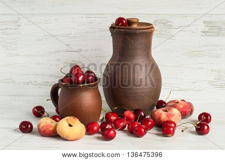 Mug with a sweet cherry, a clay pitcher,  sweet cherry and peaches on a light wooden background.