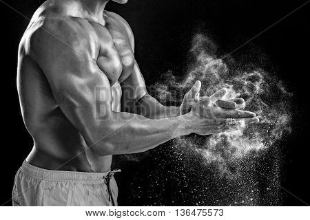 young muscular man preparing to hand lifting heavy weight. White talcum dynamically scatters in different directions.. Black and white. stands sideways. Close-up