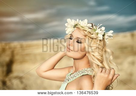 The girl in a blue dress with a wreath on his head
