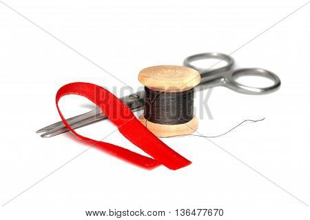 Scissors and a skein of black thread on white background