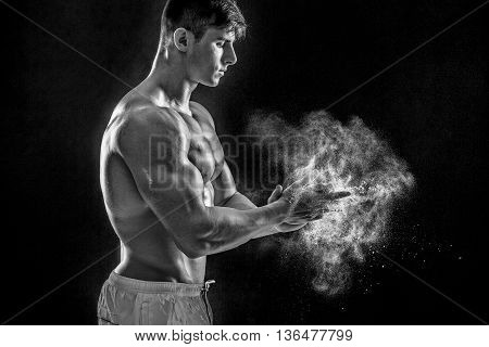 young muscular man preparing to hand lifting heavy weight. White talcum dynamically scatters in different directions. Black and white. stands sideways