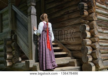 girl out on the porch of the old house and misses