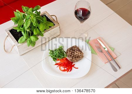 Steak with vegetables served with red wine in a restaurant