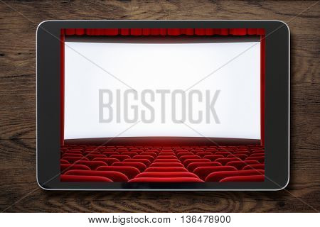 Tablet pc on wooden table with cinema screen displayed. Movies or cinema online concept.