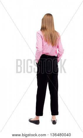 back view of standing young beautiful  woman.  girl  watching. Rear view people collection.  backside view of person.  The girl office worker in black pants standing with his hands in his pockets.