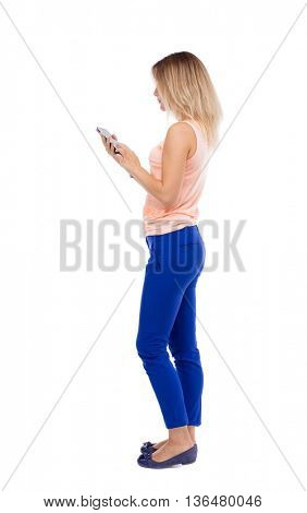 back view of standing young beautiful  girl with tablet computer in the hands of. girl  watching.  Isolated over white background. Blonde girl in blue trousers running with a tablet computer.