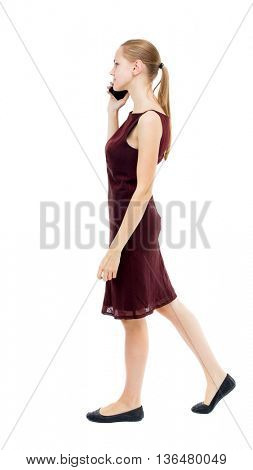 a side view of a woman walking with a mobile phone. beautiful curly girl in motion.  backside view person. Isolated over white background. girl in a burgundy dress talking on the phone and walks away