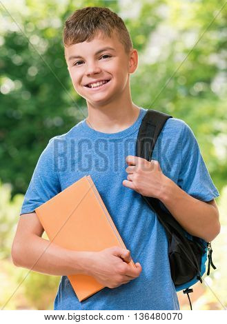 Teen boy 12-14 year old with schoolbag and book posing outdoors.