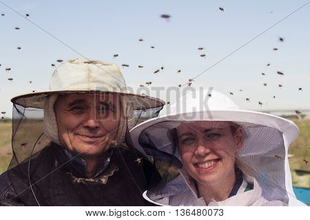 horizontal portrait of two beekeepers father and daughter surrounded by swarmming bees