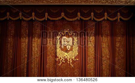 Theatrical mask on beautiful curtains  background .