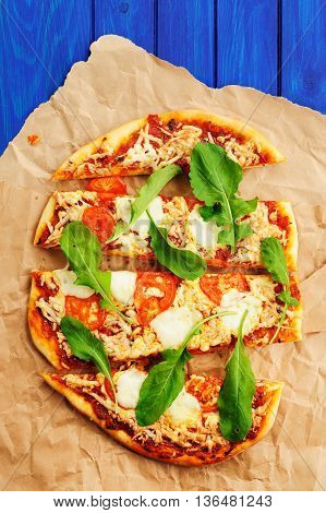 Rucola pizza on wrinkled craft paper with blue background overhead view
