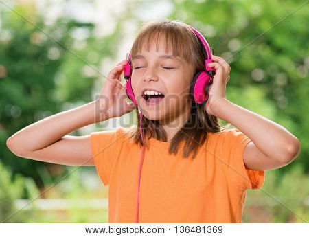 Little girl with headphones listening to music in summer park