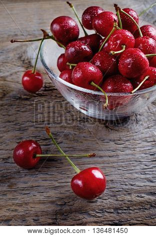 Fresh cherry berries in a transparent cup on a dark rustic wooden background