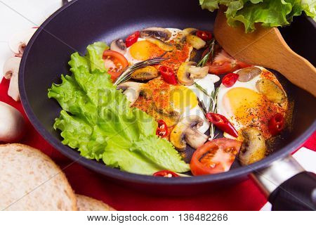 Homemade fried eggs in pan with tomato bread pepper and mushrooms on the table