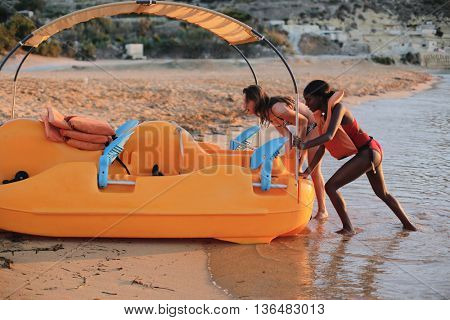Girls pushing a pedal boat on the sand