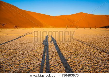 Travel to Namibia. Namib-Naukluft National Park. White bottom of a dried-up lake surrounded by orange dunes. Long shadows from people with cameras