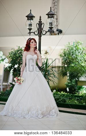 Portrait Of Charming Red-haired Bride Model With Wedding Bouquet At Hand Posed Background Lantern On