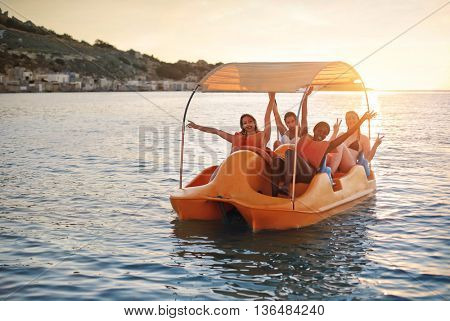 Happy girls on a pedal boat